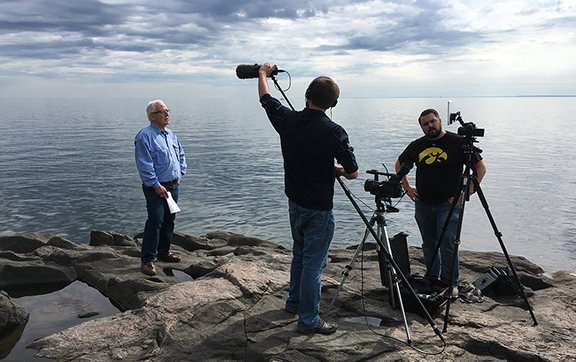 Man standing on rocky beach by Lake Superior in front of two men holding cameras and microphones.