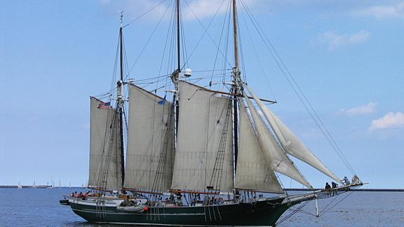 Sailing vessel Denis Sullivan on the waters of a Great Lake is a replica three-masted, wooden, gaff rigged schooner from Milwaukee, Wisconsin.