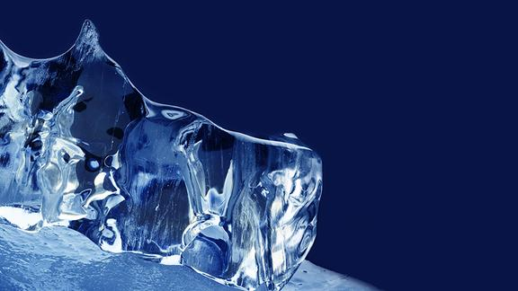 Clear, jagged chunk of ice against a dark blue background.