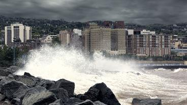 Waves crashing onto rocks in front of buildings