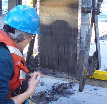 "Photo of Kathleen (""Kitty"") Kennedy sampling a sediment core on-board the R/V Lake Guardian, Lake Ontario, 2013."